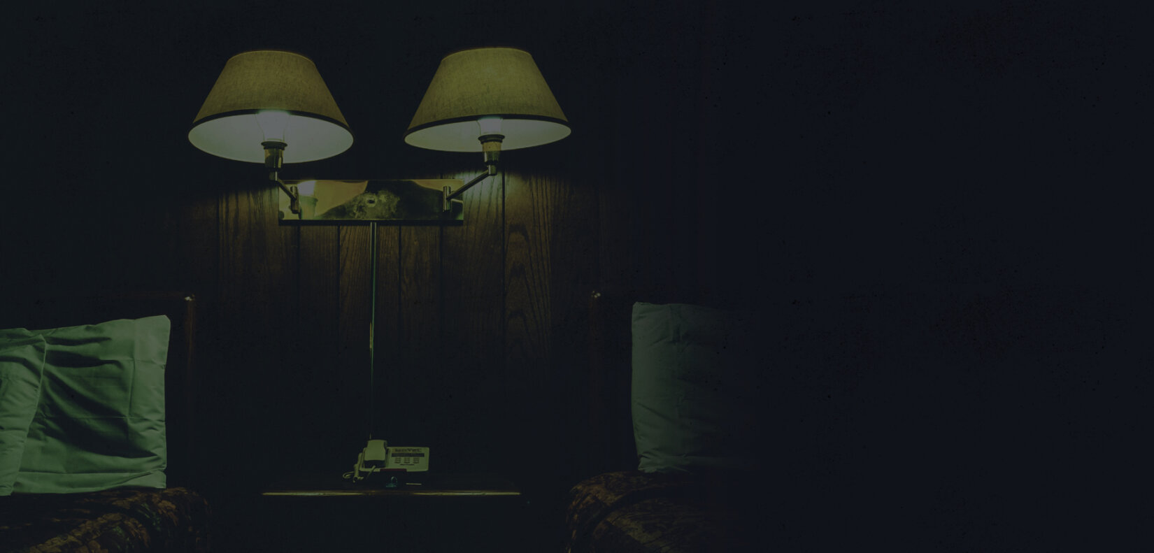 Dimmed image of hotel room with lights and night stand between two beds