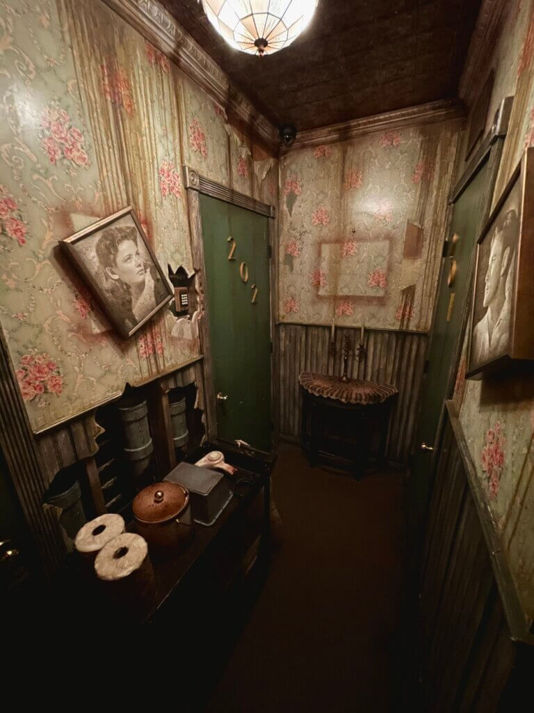 View of No Vacancy room with damaged wallpaper and dim lighting